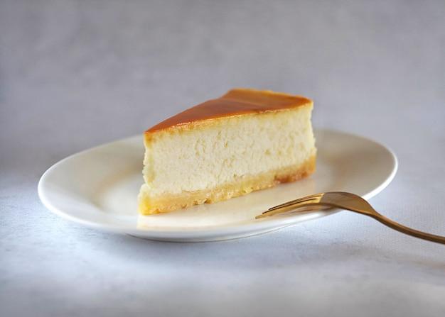 옆에 금 포크와 함께 테이블에 접시에 카라멜 치즈 케이크의 조각.
