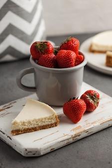 白い木の板にクルックのチーズケーキと熟したイチゴのかけら