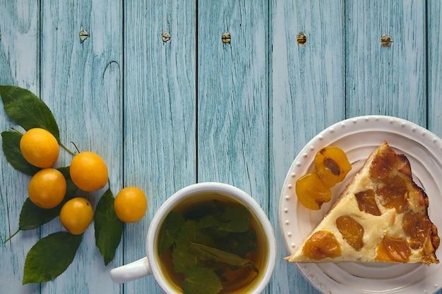 Кусок пирога из алычи с чашкой травяного мятного чая и ягодами алычи на деревянном столе, окрашенном в синий цвет. утро в саду