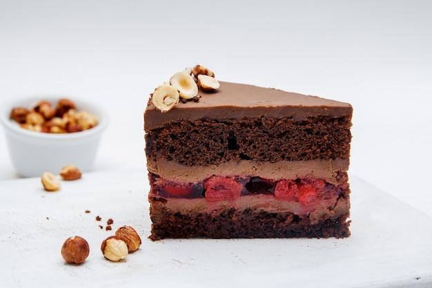 흰색 바탕에 체리와 헤이즐넛이 있는 초콜릿 케이크 한 조각. 테이블 클로즈업에 맛 있는 초콜릿 케이크입니다.