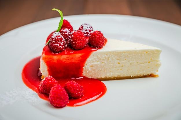 クラシックなチーズケーキニューヨーク、ラズベリーシロップのトッピング、フレッシュベリーとミントを添えて