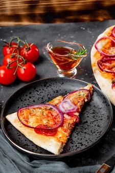 접시에 양파와 함께 고전적인 이탈리아 페퍼로니 피자 조각