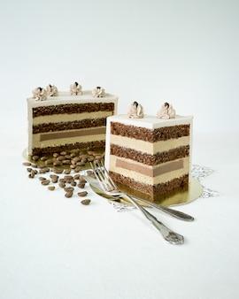 Кусок кофейного торта на белом фоне и винтажная вилка