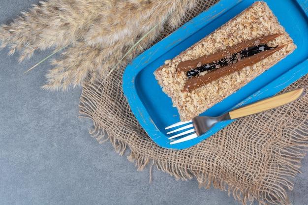 Кусок сливочного торта на синей тарелке с вилкой.