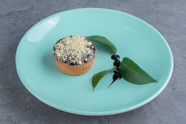 Кусочек сливочного торта с листьями на зеленой тарелке