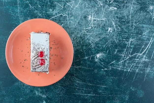 오렌지 접시에 딸기와 함께 맛있는 케이크 한 조각. 고품질 사진