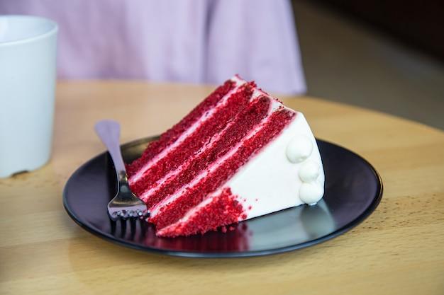 포크로 접시에 맛있는 빨간 벨벳 케이크 한 조각.