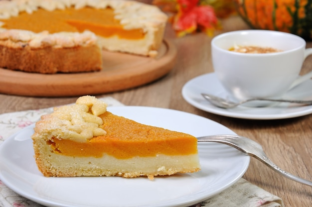 크림과 계피를 곁들인 호박 커피 한 잔과 함께 탁자 위에 있는 향긋한 호박 커드 파이 한 조각