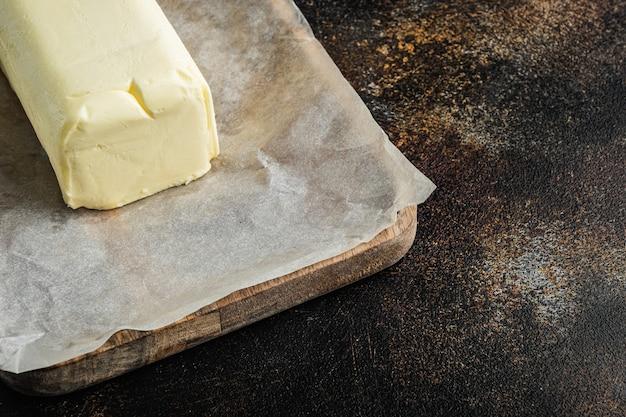 텍스트 복사 공간이 오래 된 어두운 소박한 배경에 신선한 버터 조각