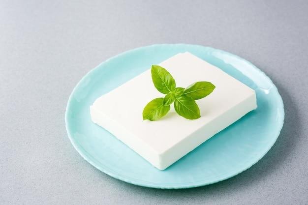 Кусок свежего сыра фета и листья базилика на тарелке на столе.