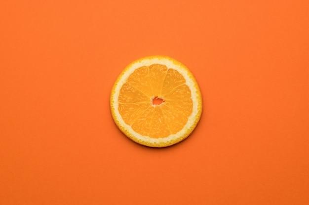 オレンジ色の背景に新鮮なオレンジの部分。人気のトロピカルフルーツ。フラットレイ。