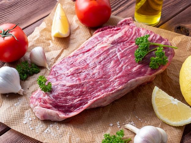 新鮮な生の牛肉は、スパイス、ハーブ、野菜に囲まれた羊皮紙の上にあります。側面図。食品組成