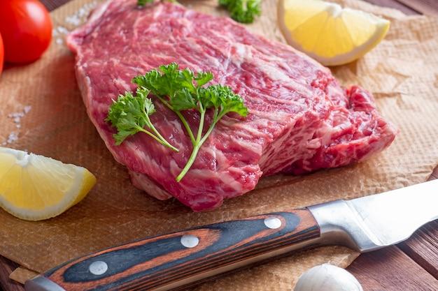 新鮮な生の牛肉は、スパイス、ハーブ、野菜に囲まれた羊皮紙の上にあります。ナイフが近くにあります。側面図。食品組成