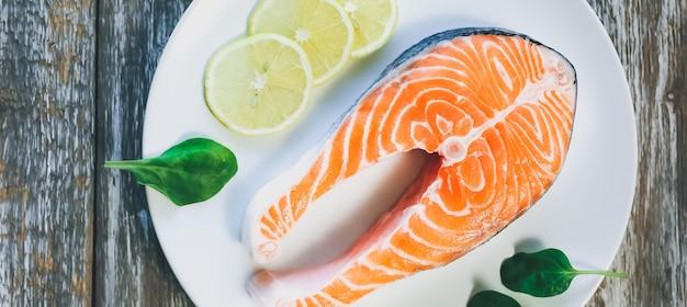 Кусок свежего стейка из лосося на белой тарелке со шпинатом и лимоном, на сером деревянном фоне. витамин омега 3, здоровый образ жизни. натуральное вегетарианское питание. вид сверху.