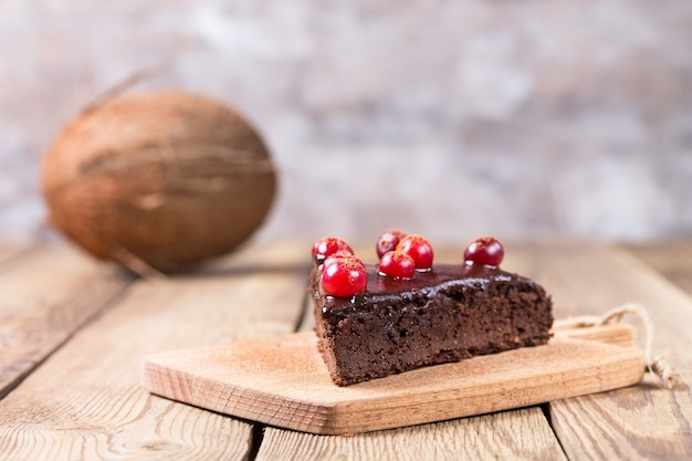 Кусок торта без глютена в шоколаде, украшенный клюквой, на размытом фоне. на заднем плане - кокос.