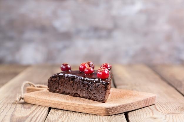 Кусок торта без глютена в шоколаде, украшенный клюквой, на кухонной доске, на размытом фоне. здоровая пища.