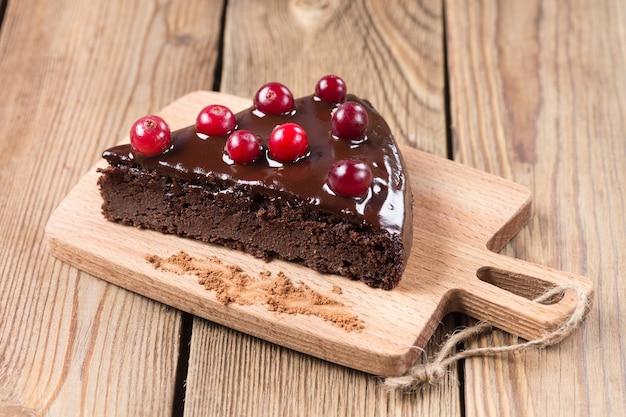 Кусок торта без глютена в шоколаде, украшенный клюквой, на кухонной доске, на деревянном фоне. здоровые десерты.