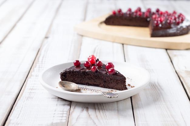 Кусок шоколадного торта без глютена, украшенный клюквой, на белой тарелке, на светлом деревянном столе. здоровые десерты.