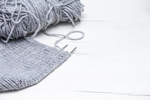 Кусок серого вязания спицами