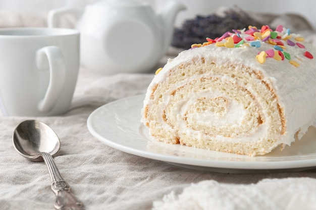 バタークリームの自家製ビスケットロール カラフルなトッピングで飾られた白い皿の上 背景には白いティーポットとマグカップ クローズアップ