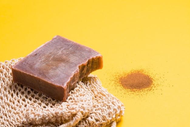 Кусок домашнего шоколадного мыла и вязаная мочалка, горсть молотого кофе на желтой поверхности