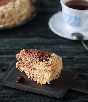 Кусок домашнего классического медового торта на деревянном столе