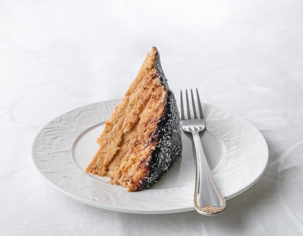 Кусок домашнего многослойного бисквитного торта, пропитанный сливочным кремом, с шоколадной глазурью и кокосом на белой тарелке с вилкой крупным планом белый фон