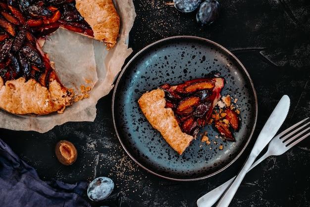 Кусок домашнего сливового пирога на черной тарелке.