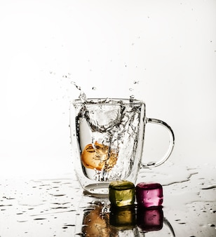 잔에 던져진 얼음 조각이 음료수를 튀겼습니다.