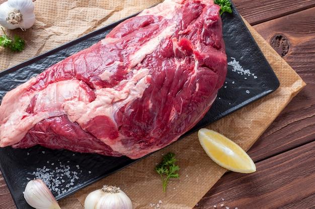 霜降り肉は、ハーブ、ニンニク、塩に囲まれた羊皮紙の上にあります。上面図、フラットレイ。食品組成