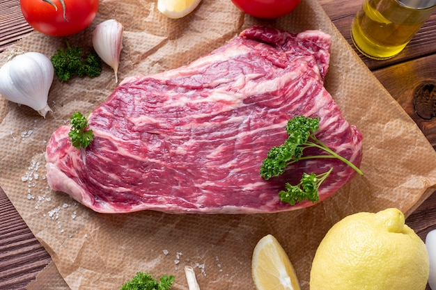 차돌박이 쇠고기 한 조각이 허브, 마늘, 소금으로 둘러싸인 양피지에 놓여 있습니다. 평면도, 평면 누워. 식품 구성