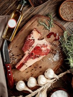 Кусок мяса для стейка на деревянной доске, посыпанный специями