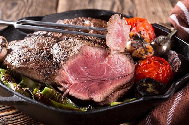 Кусок мяса на чугунной сковороде с овощами, крупным планом