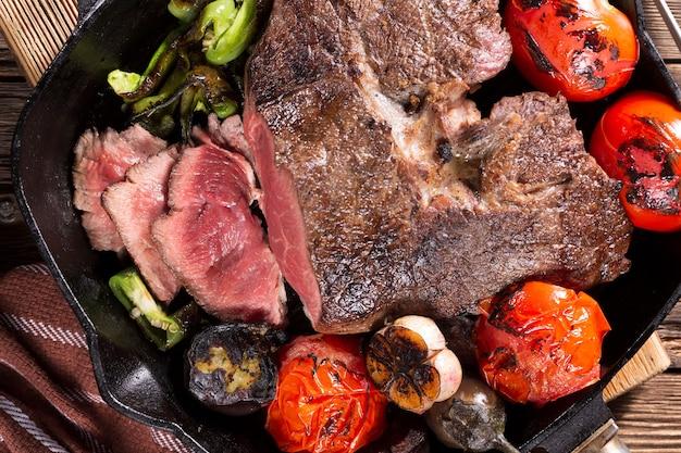 Кусок мяса, запеченный в кастрюле с овощами крупным планом
