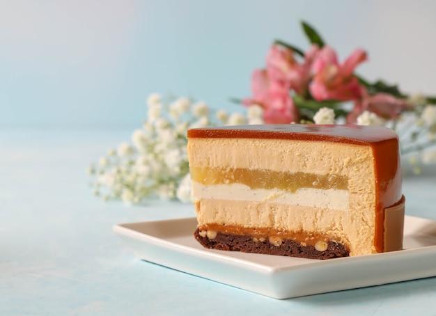 Кусок муссового торта на квадратной тарелке с цветами в