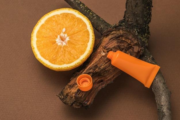 Кусочек апельсина, старое дерево и открытая туба крема на коричневом фоне.