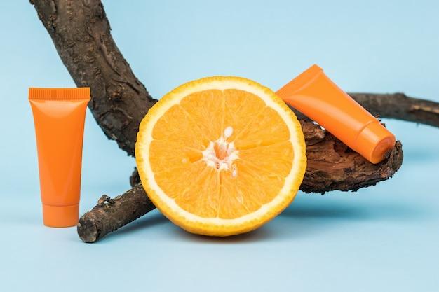 Кусок апельсина, старое дерево и две оранжевые тюбики сливок на синем фоне. косметика и лечебные мази на основе природных минералов.