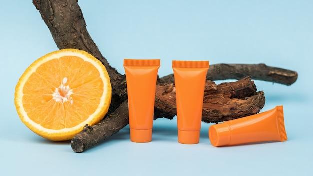 Кусочек апельсина, две тюбика сливок и старое дерево на синем фоне.
