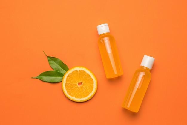 Кусок апельсина с листьями и две бутылки сока на оранжевом фоне. плоская планировка.