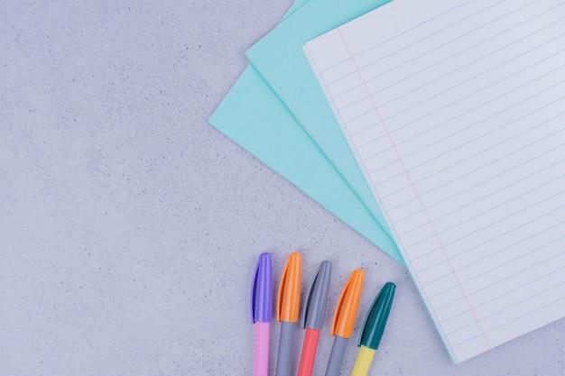 Листок бумаги с разноцветными карандашами вокруг