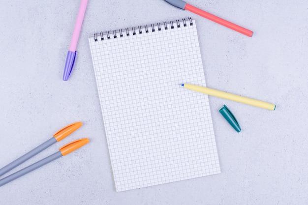 주위에 여러 가지 빛깔의 연필이있는 종이