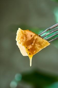 Кусок сыра пармезан, из которого льется мед
