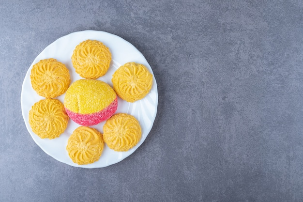 Кусок печенья и бисквита в форме персика на тарелке на мраморном столе.