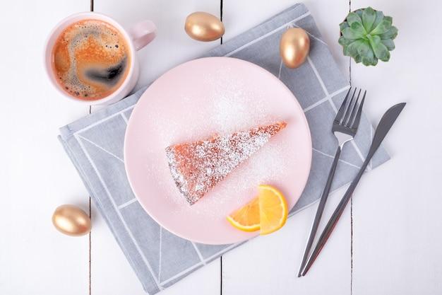 幾何学模様とコーヒーのマグカップと折り畳まれたリネンナプキンのナイフとフォークでピンクのプレート上のパイの一部