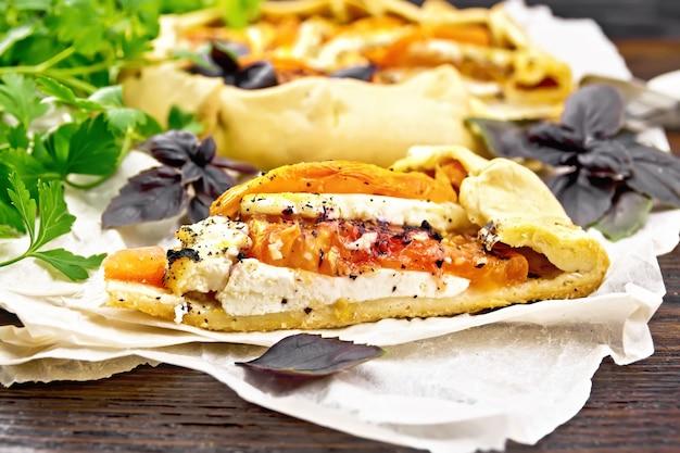 양피지에 토마토, 커드 치즈, 보라색 바질을 넣은 파이 한 조각, 어두운 나무 판자에 파슬리