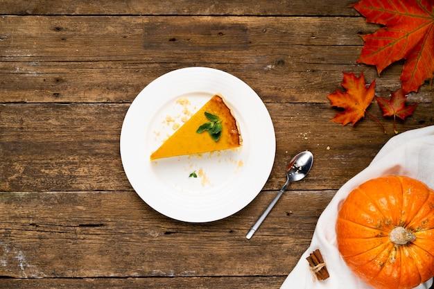 Кусок тыквенного пирога на деревянном столе в центре, тыква и осенние листья, копируют пространство.