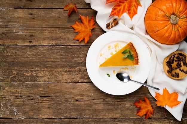 Кусок тыквенного пирога на деревянном столе справа, тыква и осенние листья, скопируйте пространство слева.