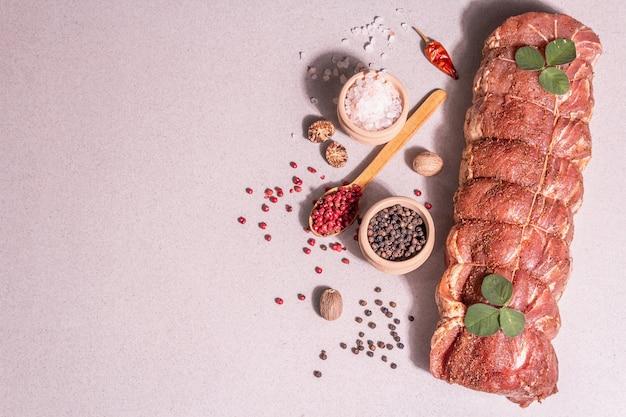 생 돼지 허리의 조각입니다. 양념과 함께 요리 꼬기로 묶인 절인 신선한 고기. 트렌디한 하드 라이트, 어두운 그림자, 석재 콘크리트 배경, 위쪽