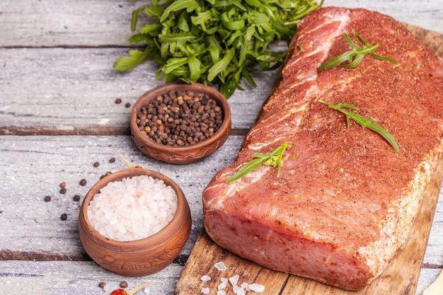 생 돼지 허리의 조각입니다. 향신료와 절인된 신선한 고기입니다. 나무 판자 배경에 칠리, 채소, 클로즈업