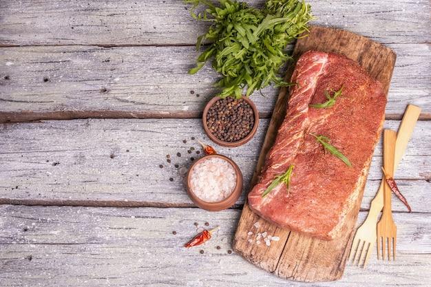 생 돼지 허리의 조각입니다. 향신료와 절인된 신선한 고기입니다. 칠리, 채소, 나무 판자 배경, 평면도
